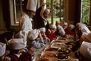 France. Lyon . Chef jean Paul Lacombe (Leon de Lyon, and the Bistrot de Lyon) with a group of primary school children during a national taste week , an annual event that gives children the chance to discover new flavours    /  Le cuisinier jean Paul Lacombe (restaurant Leon de Lyon, le bistrot de Lyon) reunit autour de lui les enfants d'une classe primaire dans le cadre de la semaine nationale du goût. Une manifestation annuelle qui est l'occasion pour les plus jeunes de decouvrir des saveurs nouvelles.   /  R00069/7    L931020a  /  P0000232