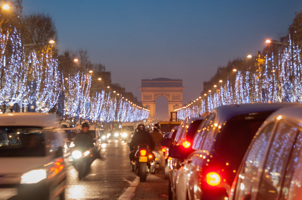 Champs Elysees at night with Arc de Triomphe in background.