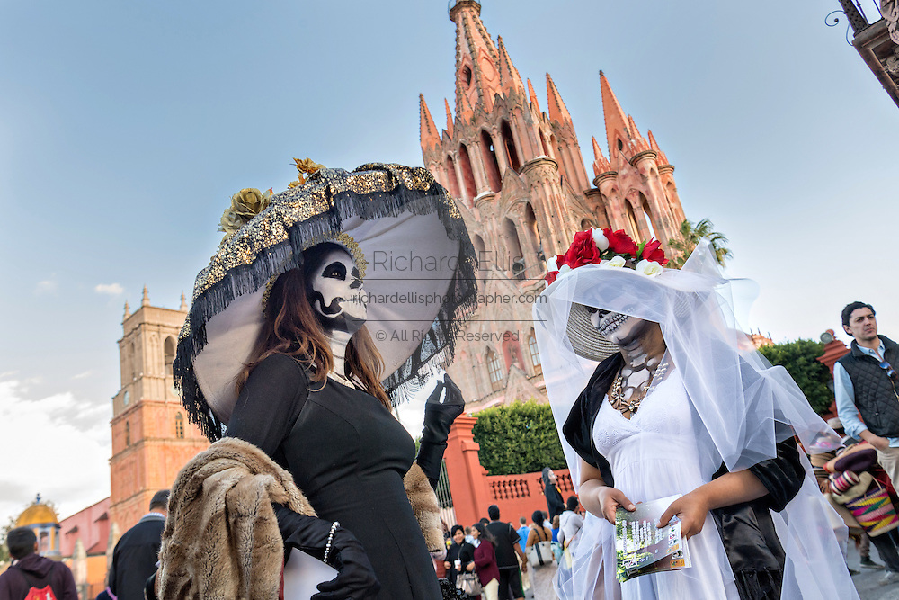 Women dressed as La Calavera Catrina in front of the La Parroquia de San Miguel Arcangel church during the Day of the Dead festival October 28, 2016 in San Miguel de Allende, Guanajuato, Mexico. The week-long celebration is a time when Mexicans welcome the dead back to earth for a visit and celebrate life.