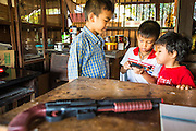 13 JANUARY 2013 - BANGKOK, THAILAND:  Boys play with a smart phone while their toy gun sits in front of them in the Bang Luang neighborhood of Bangkok. The Bang Luang neighborhood lines Khlong (Canal) Bang Luang in the Thonburi section of Bangkok on the west side of Chao Phraya River. It was established in the late 18th Century by King Taksin the Great after the Burmese sacked the Siamese capital of Ayutthaya. The neighborhood, like most of Thonburi, is relatively undeveloped and still criss crossed by the canals which once made Bangkok famous. It's now a popular day trip from central Bangkok and offers a glimpse into what the city used to be like.   PHOTO BY JACK KURTZ