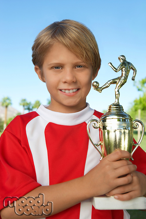 Boy (7-9 years) soccer player holding trophy, portrait