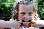 flower girl teasing the photographer during a wedding at the lake of the Ozarks, Missouri
