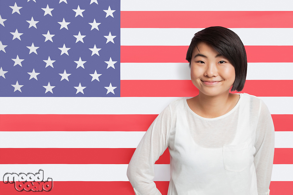 Portrait of young Asian woman smiling against American flag