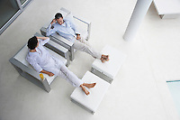 Couple sitting in side by side armchairs on terrace elevated view