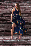 Houston fashion model Rachael Campbell modeling long sundress in front of wall of weathered railroad timbers by Gerard Harrison, photographer, Image Theory Photoworks