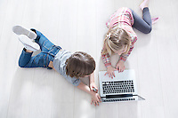 High angle view of brother and sister using laptop on floor at home