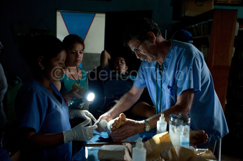 Doctor (and priest) Jack Mc. Carthy co-founder of  Centro de Salud of Santa Clotilde, during an emergency surgery on a machete wound. Like in many villages of amazonic basin, at Santa Clotilde too the electric lights it's not all the day furnished.