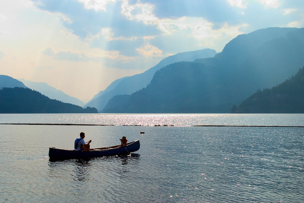 A  canoe glides softly over Upper Campbell Lake BC