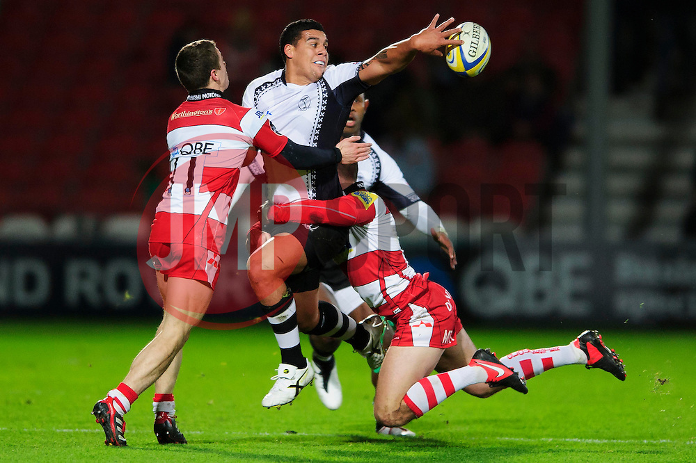 Fiji Inside Centre (#12) Josh Matavesi passes as he is tackled by Gloucester Full Back (#15) Martyn Thomas and Winger (#11) Ian Clark during the first half of the match - Photo mandatory by-line: Rogan Thomson/JMP - Tel: Mobile: 07966 386802 13/11/2012 - SPORT - RUGBY - Kingsholm Stadium - Gloucester. Gloucester Rugby v Fiji - International Friendly