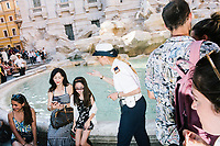"""ROME, ITALY - 20 JUNE 2017: A Roman policewoman, entrusted to protect the Fountain of Trevi, orders tourists to not sit on the edge of the fountain in Rome, Italy, on June 20th 2017.<br /> <br /> The warm weather has brought a menacing whiff of tourists behaving badly in Rome. On April 12, a man went skinny-dipping in the Trevi fountain resulting in a viral web video and a 500 euro fine.<br /> <br /> Virginia Raggi, the mayor of Rome and a national figurehead of the anti-establishment Five Star Movement,  issued an ordinance involving harsher fines for eating, drinking or sitting on the fountains, for washing animals or clothes in the fountain water or for throwing anything other than coins into the water of the Trevi Fountain, Bernini's Four Fountains and 35 other city fountains of artistic or historic significance around the city.  """"It is unacceptable that someone use them to go swimming or clean themselves, it's an historic patrimony that we must safeguard,"""" Ms. Raggi said."""