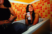 Two girls sitting in a bath drinking at Budweiser house party at Manchester Academy UK 2000