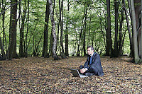 Business man sitting on ground using laptop in middle of forest
