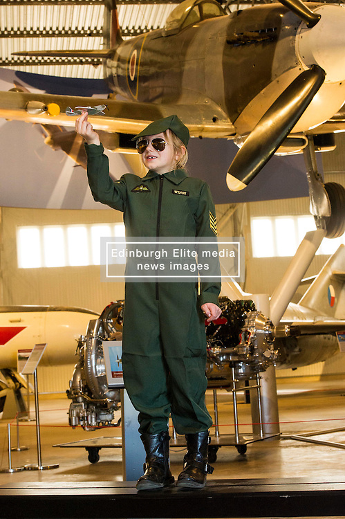 Pictured: Hannah age 7, from Athelstaneford Primary School tests out her wings under a Spitfire<br /> <br /> The redeveloped National Museum of Flight at East Fortune has undergone a  £3.6 million refurbishment and now has aeroplanes including a Spitfire, a Harrier Jump Jet and a Tornado T-3 on display.    (c) Ger Harley, EEm 22 March 2016