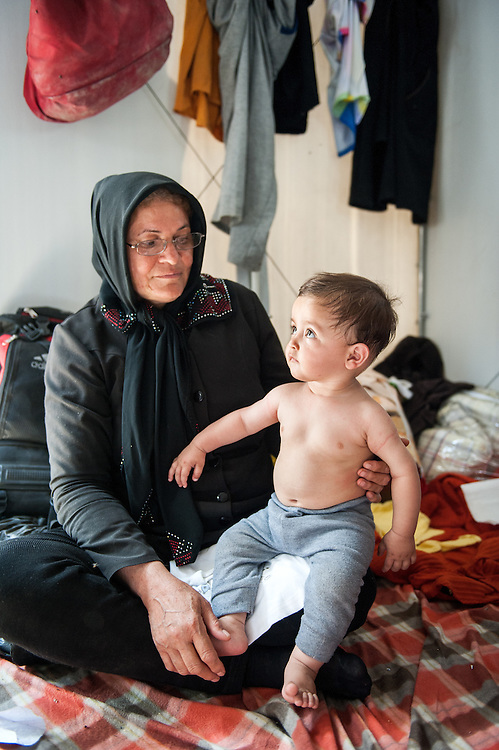 Nazime 46 years old from Herat Afghanistan holding her 8 month old grandson Mahdi in Moria camp, Lesvos, Greece