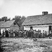 Plantation slaves gathered outdside their huts, Virginia, America. Photograph c1860.