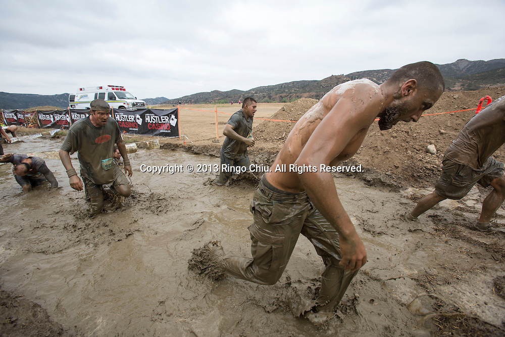 Runners cross the mud pit during the Irvine Lake Mud Run on Saturday, April 6, 2013 in Orange County, California.  More than 4000 runners competed at the Mud Run, a 5k off-road course traversing trails, and hills, starting and finishing at Irvine Lake in Silverado Canyon. (Photo by Ringo Chiu/PHOTOFORMULA.com)