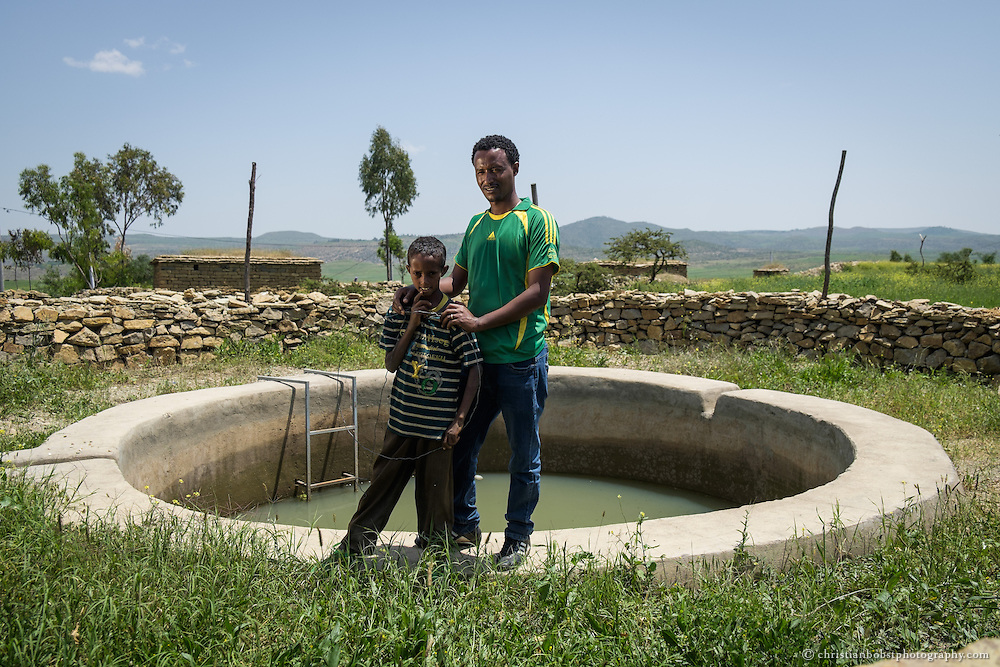 Beles Sunrise project BSP, rain water harvesting, Mogos Kalayu (13), grade 7, and school director Berihu Hailu (29) pose in front of school pond.