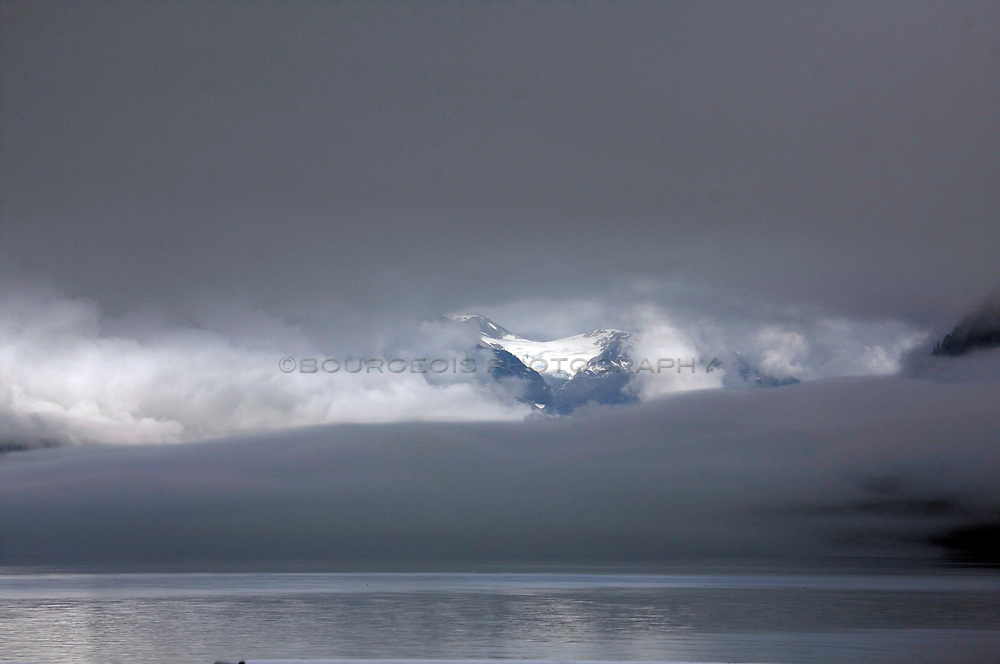 Southeast Alaska fishing boat heads into heavy clouds and fog while a glacier sits and retreats.