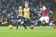 Arsenal's Aaron Ramsey makes a pass under pressure during the Barclays Premier League match between Aston Villa and Arsenal at Villa Park, Birmingham, England on 13 December 2015. Photo by Shane Healey.