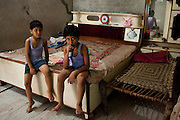 Seema Gupta's children aged 8 and 10 watch television in their shophouse in Ghaziabad, Uttar Pradesh, India. Seema Gupta, aged 34 (unseen), had a tubectomy done on 9 June 2011 for family planning while her husband, Ramesh Chandra Gupta, aged 38 (unseen), wasn't aware of the option and benefits of non-scalpel vasectomy (NSV). They run a roadside sweets shop at the front of their house and chose to have a family planning surgery done as they did not want to compromise the quality of life for their two children. While Ramesh wanted only 1 child, both his mother and Seema pushed for a 2nd child. Photo by Suzanne Lee / Panos London