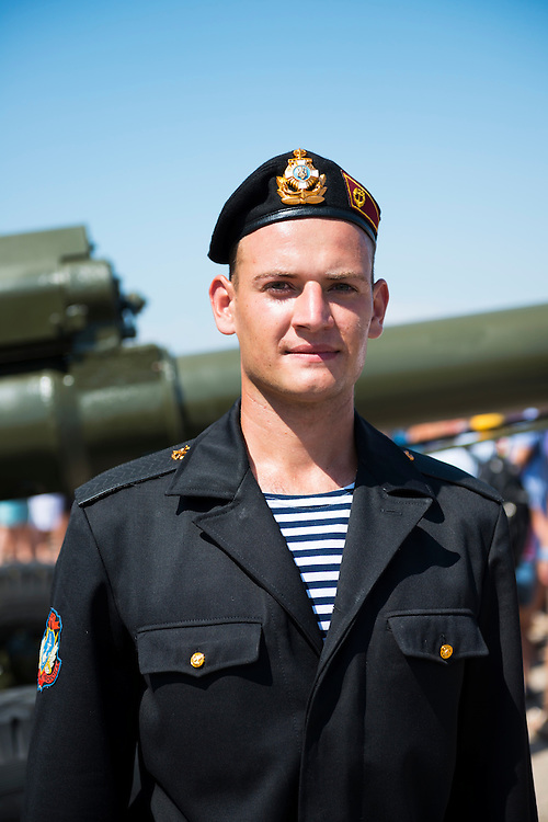 Portrait of a Ukrainian sailor standing in front of an artillery piece in Sevastopol, Crimea, Ukraine. Photo taken during the annual Navy Day event. Sevastopol is home to both Russian and Ukrainian forces. (Sevastopol, Crimea, Ukraine - July 28, 2013)