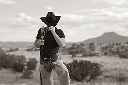 cowboy tipping his hat over his head outdoors in New Mexico