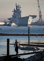 © Licensed to London News Pictures. 1/12/2016. Portsmouth, UK. A man pulls a dinghy down a ramp as tugs move the former Royal Navy aircraft carrier HMS Illustrious from Portsmouth Naval Base out into the harbour ahead of her final voyage to a scrap yard.  Illustrious, the last of the Invincible Class carriers, has been sold to the Leyal Ship Recycling and Dismantling company in Aliaga, Turkey - the same yard that dismantled her sister ships Ark Royal and Invincible. Photo credit: Peter Macdiarmid/LNP