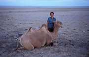 Mongolia, Gobi desert. July 1996: One of Munkhtsetseg's family poses with a camel in the Gobi desert.