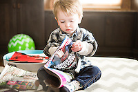 A 2-year-old boy reads magazine at home.
