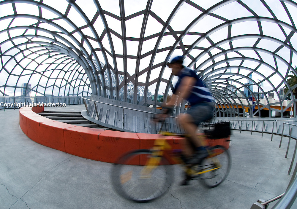 Cyclist crossing dramatic steel Webb Footbridge in Doclands Melbourne Australia