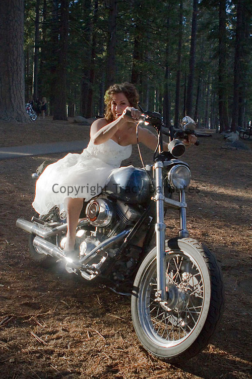 Smiling bride in wedding dress on a motorcycle before her Northern California outdoor wedding.