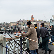 Fishermen line the edge of Galata Bridge with their lines over the side into the Golden Horn. Spanning the Golden Horn and linking Eminonu with Karakoy, the Galata Bridge is a dual-level bridge that handles road, tram, and pedestrian traffic on the top level with restaurants and bars on the level below.