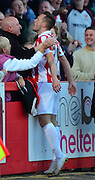 Shaun Harrad celebrates with the fans after scoring the first goal during the Sky Bet League 2 match between Cheltenham Town and Cambridge United at Whaddon Road, Cheltenham, England on 14 April 2015. Photo by Alan Franklin.