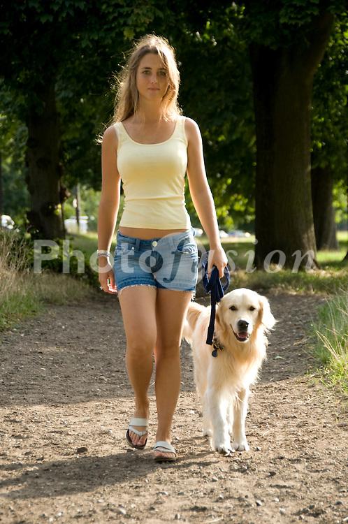 Young woman walking her dog UK
