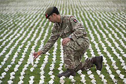 © Licensed to London News Pictures. 07/11/2018. London, UK.British soldier Captain James Pugh bows amongst tens of thousands of shrouds during the unveiling of British artist Rob Heard's exhibit 'Shrouds of the Somme' ahead of Armistice Day in London, Britain, 07 November 2018. All 72,396 shrouds that represent the soldiers who were never recovered during World War I are laid out shoulder to shoulder at London's Queen Elizabeth Olympic Park to mark the centenary of Armistice Day. Photo credit: Ray Tang/LNP