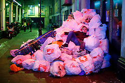© Licensed to London News Pictures. 01/01/2017. London, UK. A man lies on rubbish bags as revellers celebrate the New Year in central London during the first hours of 2017 on January 1. Photo credit: Tolga Akmen/LNP