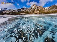 Mt Abraham at sunrise and methane ice bubbles under clear ice on Abraham Lake near Nordegg, Alberta, Canada