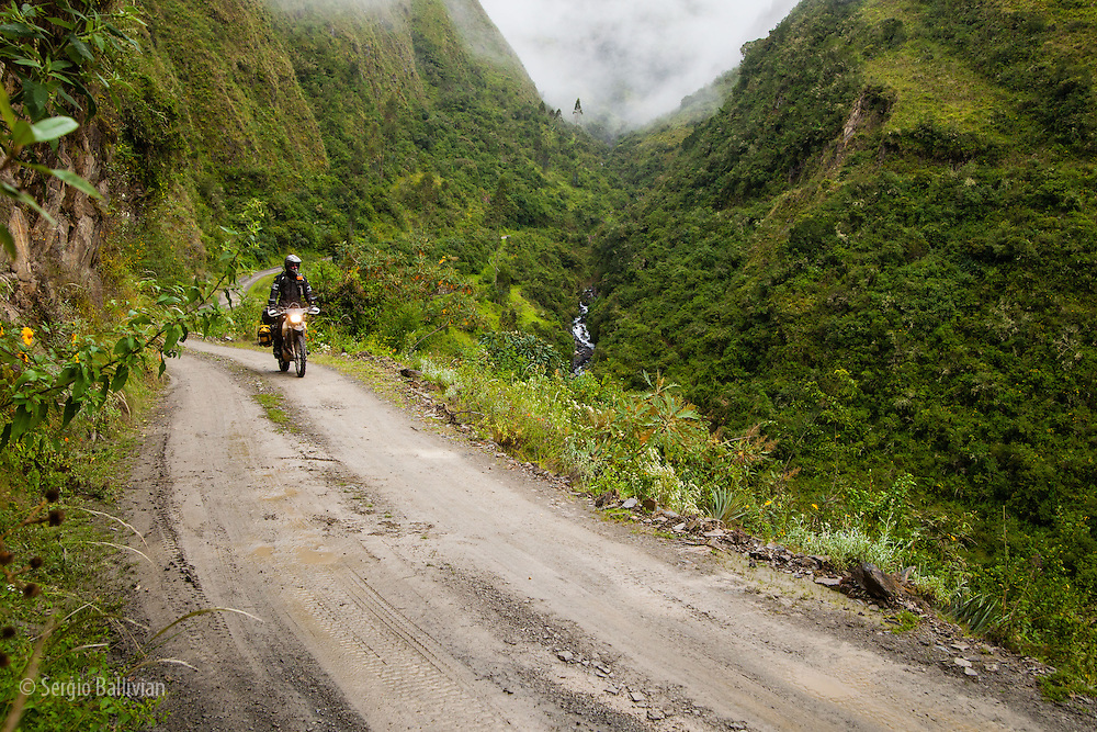 Bill Dragoo skillfully rides his adventue bike through muddy puddles and unseen obstacles while riding through the semi-tropical South Yungas region of the Bolivian Andes.