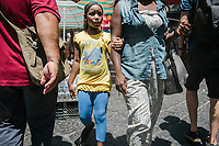 NAPLES, ITALY - 13 JULY 2017: A girl holds her mothers' arm in the Porta Capuana market in Naples, Italy, on July 13th 2017.