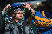 Erik Gorsack participants in a hooding ceremony at fall comment. Photo by Ben Siegel