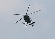A county police helicopter hovers in a blue sky.