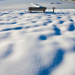 A bench on the beach on Swanzey Lake in Swanzey, New Hampshire.  Winter.