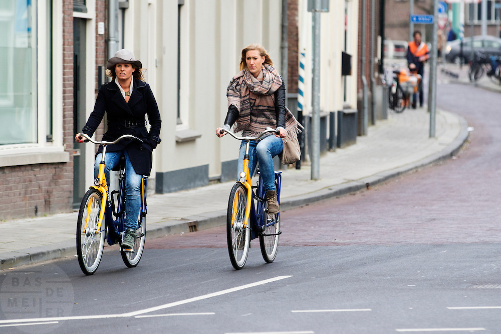 In Utrecht rijden twee vrouwen op de OV-fiets, de huurfiets van de NS.<br /> <br /> In Utrecht two women ride on the OV-bike, the rental bike of the Dutch railways.