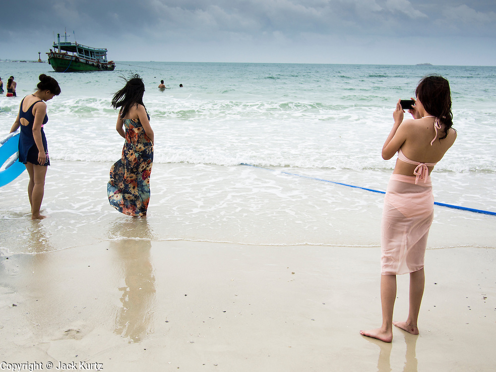 30 JULY 2013 - KOH SAMET, RAYONG, THAILAND:  Tourists play in the surf at Ao Phia beach on Koh Samet island. This part of the island was not impacted by the oil spill that fouled the west side of the island. About 50,000 liters of crude oil poured out of a pipeline in the Gulf of Thailand over the weekend authorities said. The oil made landfall on the white sand beaches of Ao Prao, on Koh Samet, a popular tourists destination in Rayong province about 2.5 hours southeast of Bangkok. Workers from PTT Global, owner of the pipeline, and up to 500 Thai military personnel are cleaning up the beaches. Tourists staying near the spill, which fouled Ao Prao beach, were evacuated to hotels on the east side of the island, which was not impacted by the spill. PTT Global Chemical Pcl is part of state-controlled PTT Pcl, Thailand's biggest energy firm.     PHOTO BY JACK KURTZ