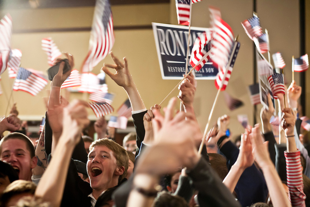 People cheer for Republican presidential candidate Ron Paul as they watch election returns at a caucus night rally on Tuesday, January 3, 2012 in Ankeny, IA.