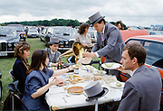 Racegoers in traditional top hats and tails have picnic with old-fashioned gramophone at Epsom Racecourse on Derby Day, UK