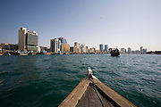 Dubai Creek. Abra (water taxis) encountering a dhow in front of Deira skyline.
