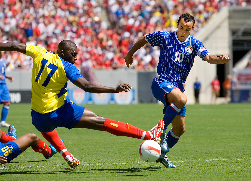 United States' Landon Donovan (R) kicks the ball around the outreached leg of Ecuador's Giovanny Espinoza during the first half of their international friendly soccer match in Tampa, Florida March 25, 2007. REUTERS/Scott Audette (UNITED STATES)