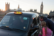 With a setting sun, Big Ben and the Houses of Parliament in the distance, two passengers ask a taxi driver his fare on Westminster Bridge awaiting a fare, on 30th November 2016, in London, England.