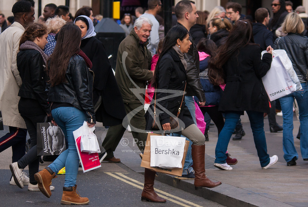 """London, December 23rd 2014. Dubbed by retailers as the """"Golden Hour"""" thousands of shoppers use their lunch hour to do some last minute Christmas shopping in London's West End. PICTURED: Shoppers carry their many bags as retailers rake in the Christmas pounds."""